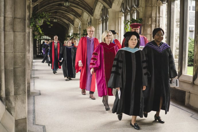 faculty in robes walking down hallway